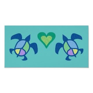 Two blue sea turtle with a four colored peace symbol on their backs