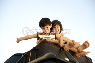 Two little boys traveling on bags, the top of the car  Foto stock